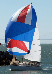 Sailboat rounding breakwater with spinnaker sail and main