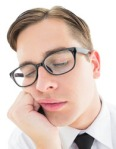 Geeky hipster falling asleep on hand on white background